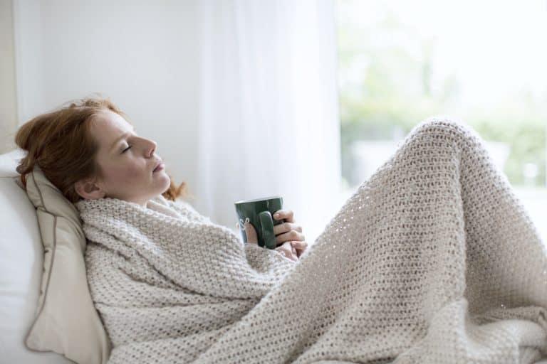 Frau erkältet unter der Decke mit Tasse Tee